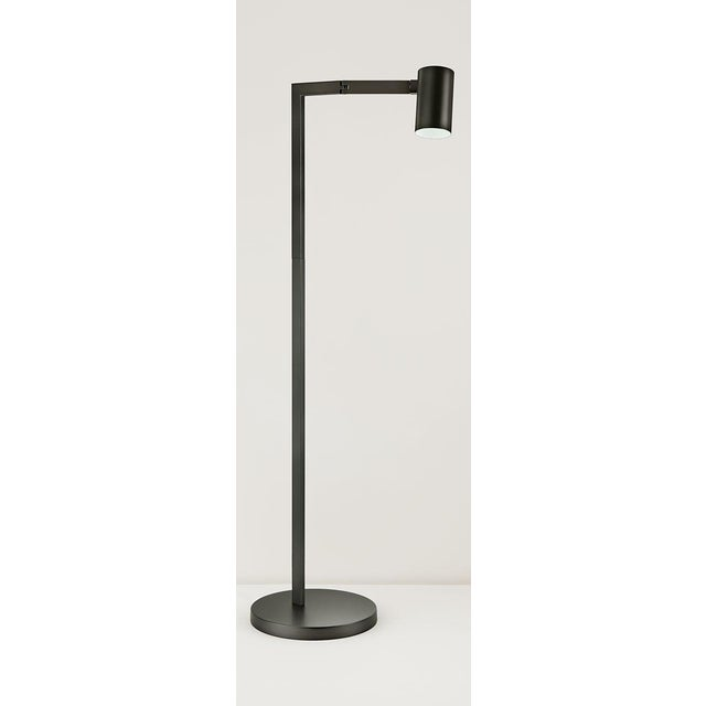 A black bronze floor reading lamp with a robust detailed hinge that allows the arm to swivel outwards. The cylindrical...