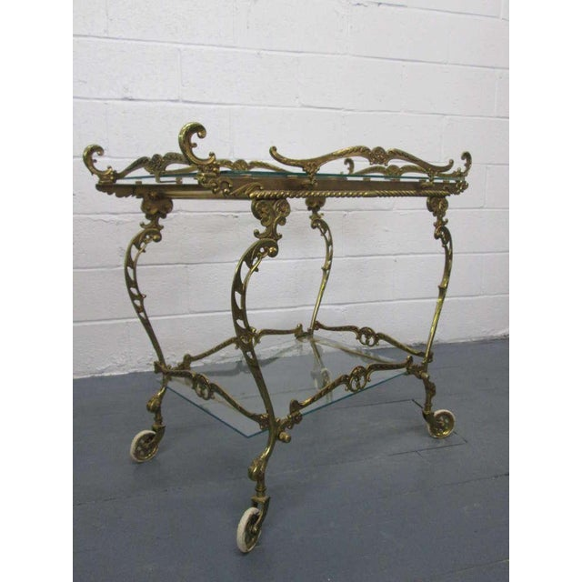 Stunning Baroque style brass bar cart with a glass top and bottom shelf. Cart has beautiful detail. Trolley.