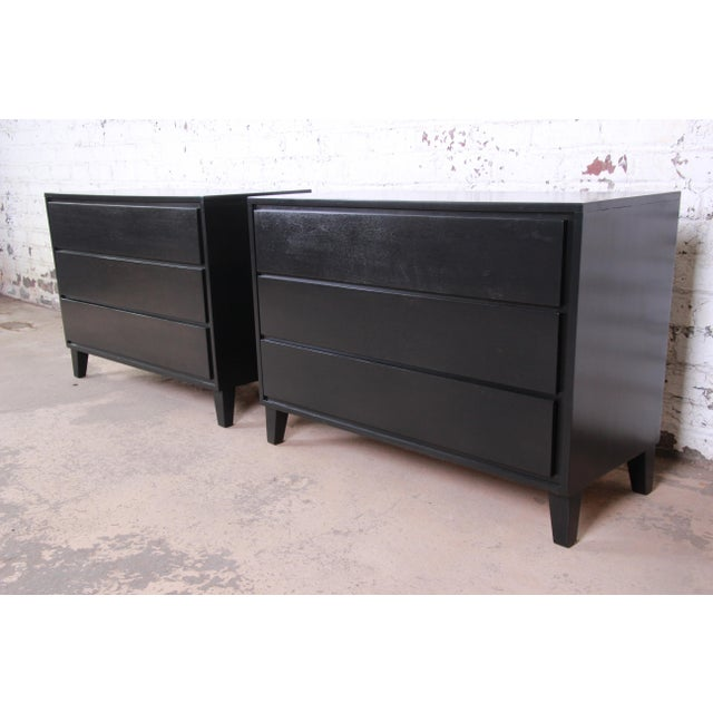 An exceptional pair of ebonized three-drawer dressers or bedside chests designed by Russel Wright for his American Modern...