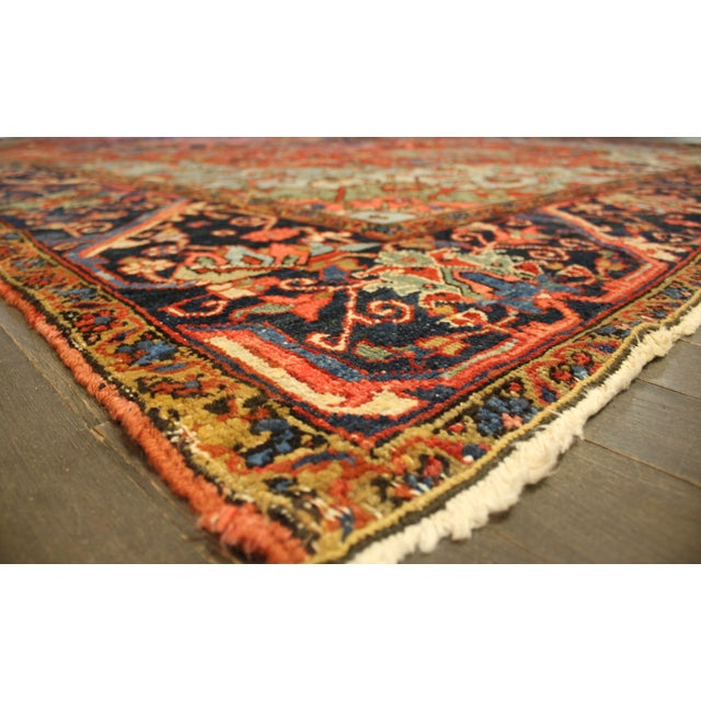 A vintage, hand-knotted Heriz rug with a geometric medallion motif on a rust field. This gorgeous rug has magnificent...