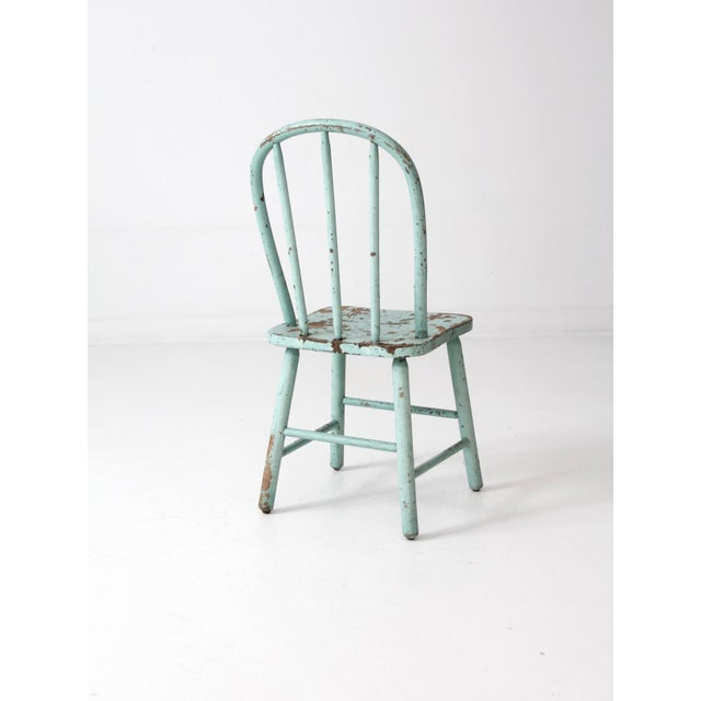 This is a vintage children's spindle back chair. The classic farmhouse chair has beautiful natural wear to its eggshell...