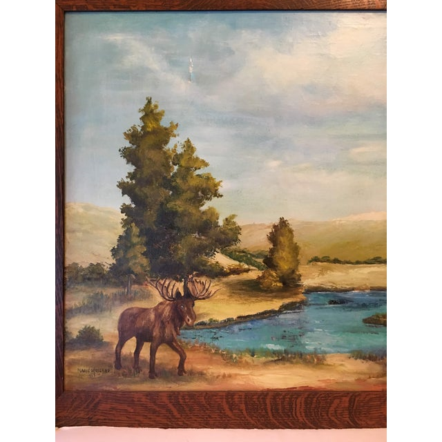 Large oil on canvas of a large moose beside a crystal blue lake and beautiful tree landscape. Framed in a large tiger oak...