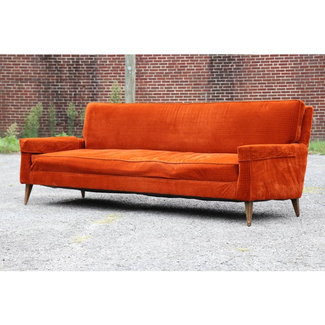 1950's Paul McCobb for Custom Craft upholstered sofa. This piece has has a sleek design with tapered legs and orange...