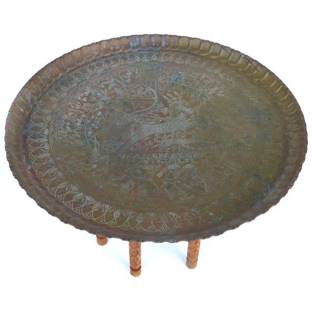 Offered for sale is a vintage Moroccan round brass tray table on a folding Stand. The ornate carved wood folding stand...