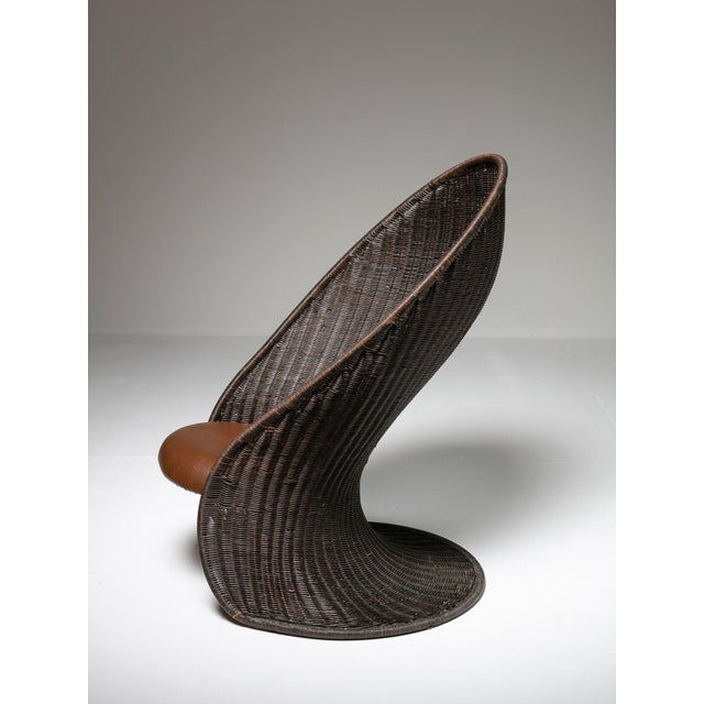 """Foglia"" lounge chair by Giovanni Travasa for Vittorio Bonacina. The piece features an enclosing wicker shell with leather..."