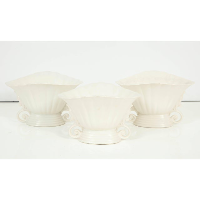 A set of three white mat-glazed Wade vases. England, circa 1930. The scalloped rim and lovely sculptural details make...