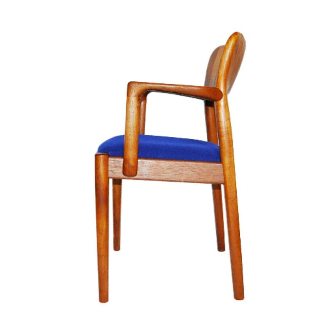 One solid teak Danish arm chair by Koefoeds Hornslet. In the style of mid century modern featuring new blue Danish wool...