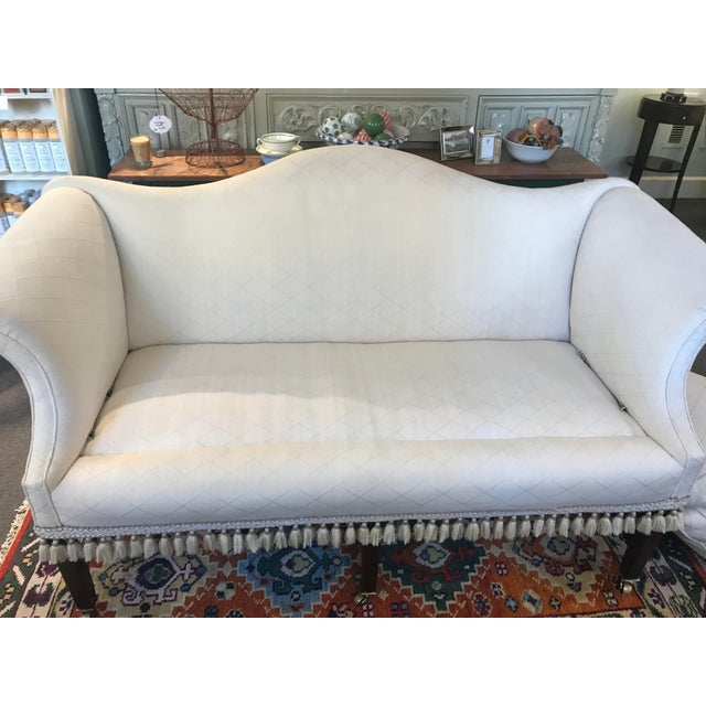 This antique mahogany stretcher is a federal style camelback love seat/settee from the 1800s designer fabric with a...
