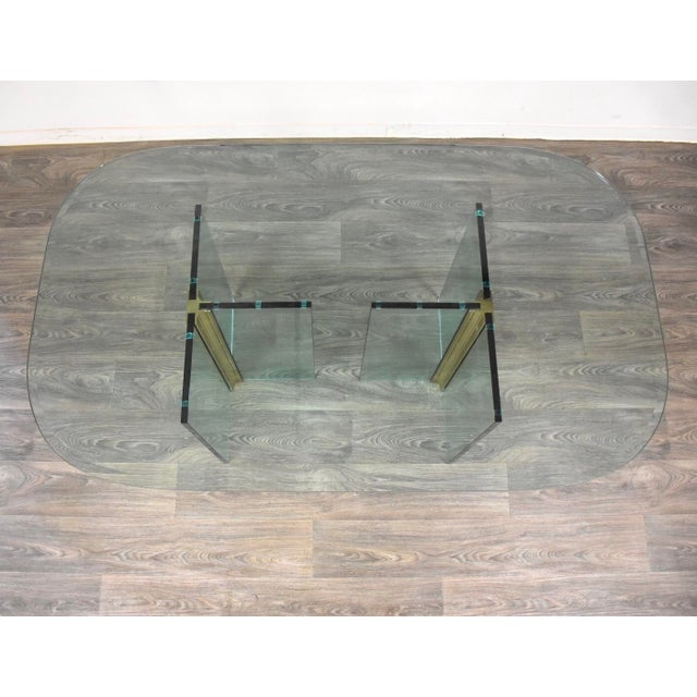 """A modern dining table constructed of glass with polished ribbed brass connector pieces forming two T shaped bases. 3/4""""..."""