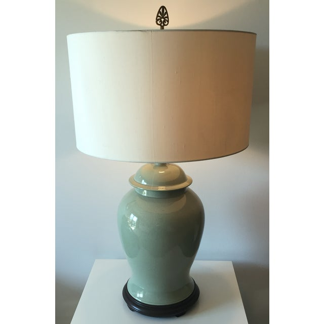A large dramatic vintage celadon crackle glazed ginger jar shaped lamp with wood pedestal base, harp and finial makes a...