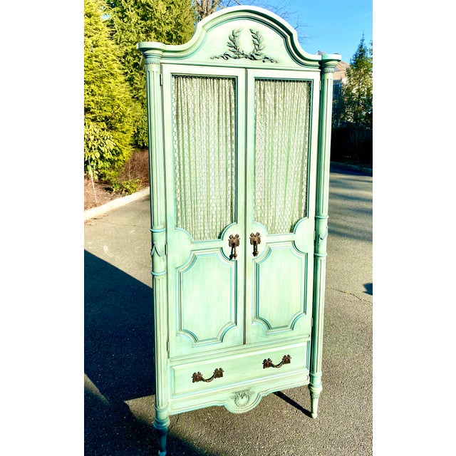 Stylish custom painted armoire by Louis Mittman, circa 1960s. Meticulous craftsmanship with traditional carved motifs and...