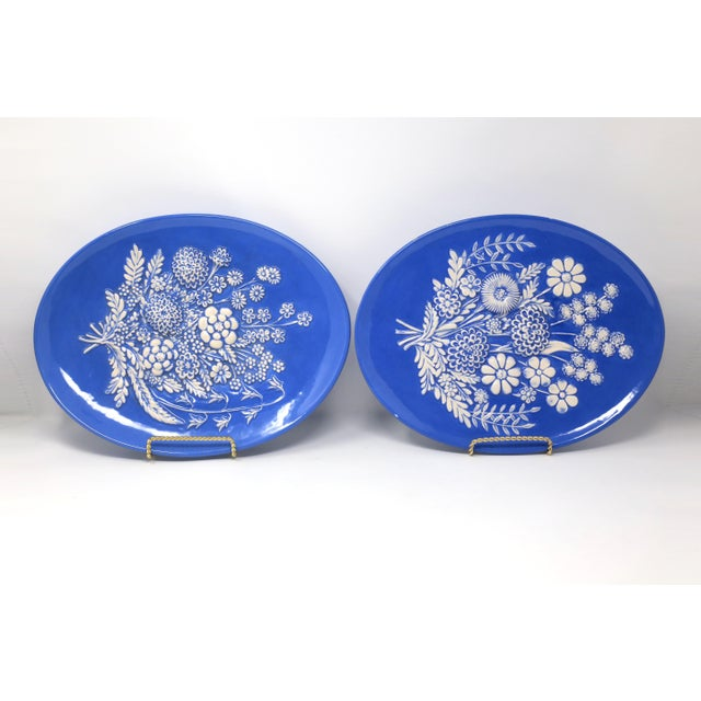A vintage set of two plates with raised white flower designs on a blue background. Good vintage condition; one plate has a...