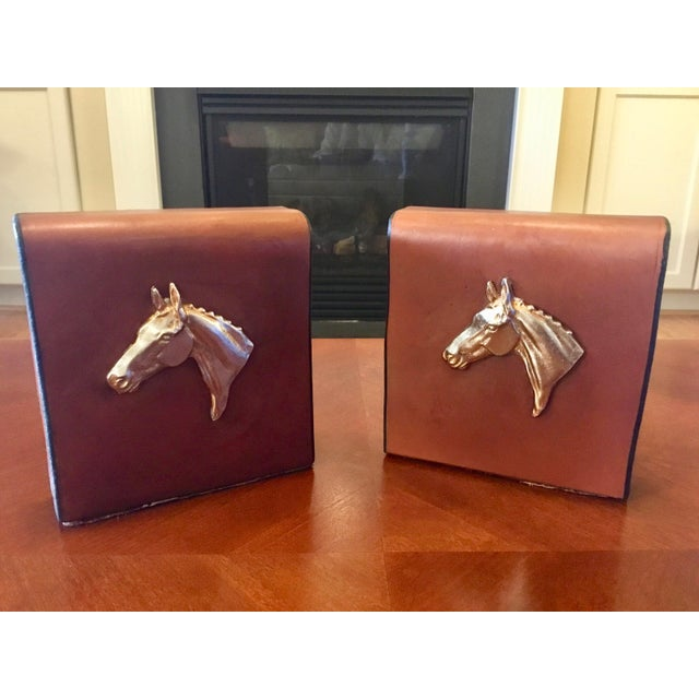 A pair of handsome English book ends, circa 1970s. Constructed of a supple tan saddle leather with black edges. Metal...