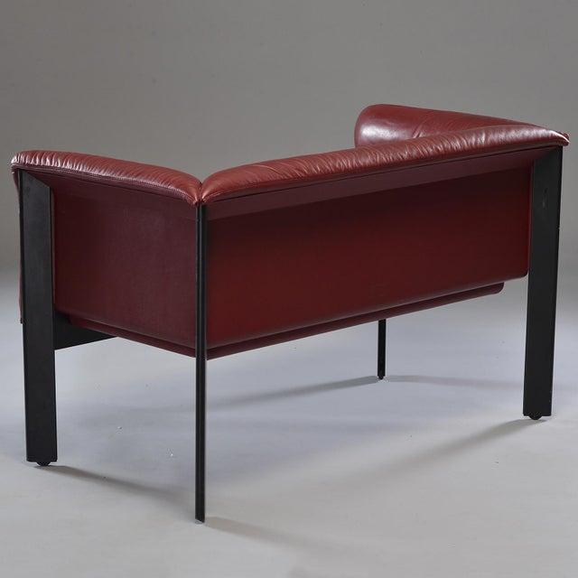 Circa 1970s burgundy leather settee by Italian maker Poltrona Frau. Black metal legs have casters. Leather on back is...