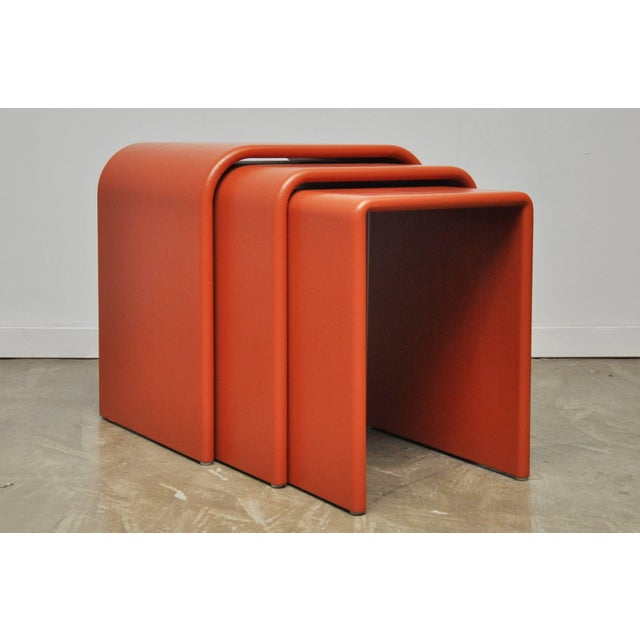 Set of three Eel Skin nesting tables. Waterfall form tables wrapped in coral dyed eel skin, circa 1970s.