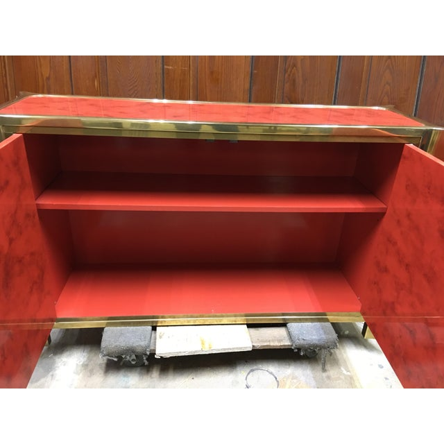 Fabulous Mastercraft lacquered and brass cabinet. Great red color decorated with brass and floral design. Opens to reveal...