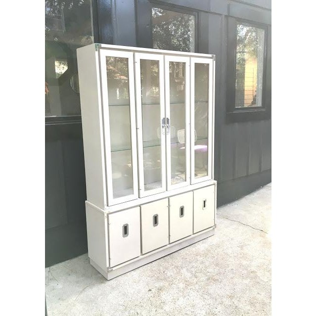 Vintage 1970s Bernhardt Furniture ivory campaign china cabinet with glass shelves and lighting inside. Plugs in to outlet...