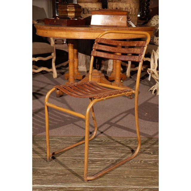 Pair of stackable painted bakelite slat chairs with painted metal tubular frames marked PEL. These industrial stacking...