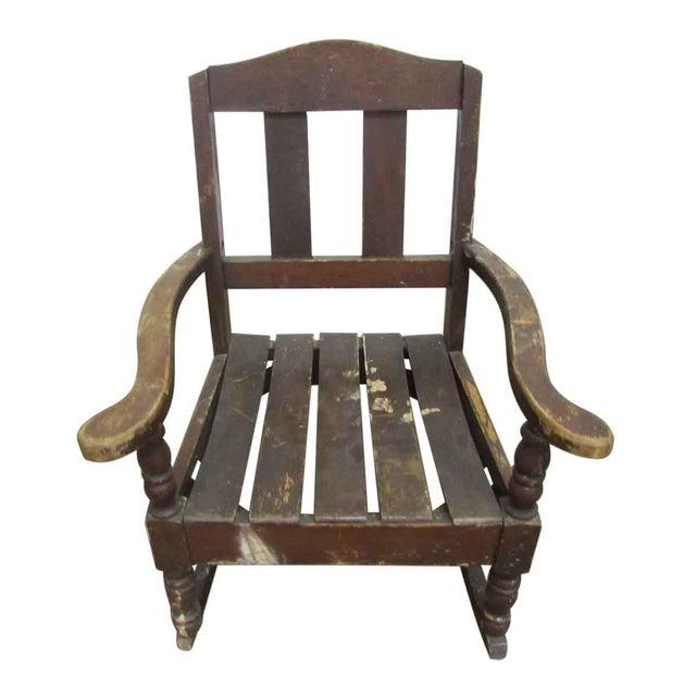 An antique petite wooden rocking chair.