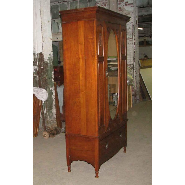 19th century carved American armoire. This piece has been kept in astoundingly good condition. The original beveled mirror...