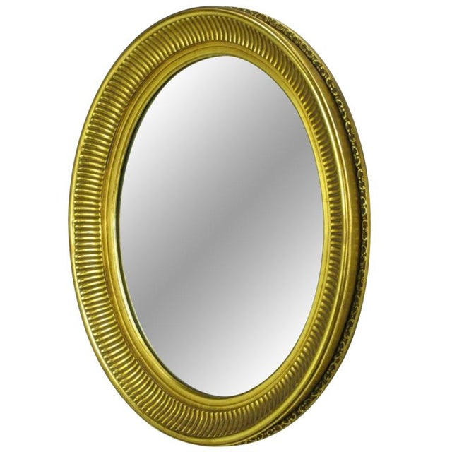Hand carved from heavy wood, and beautifully finished in aged gold leaf, this oval French regency mirror is both...