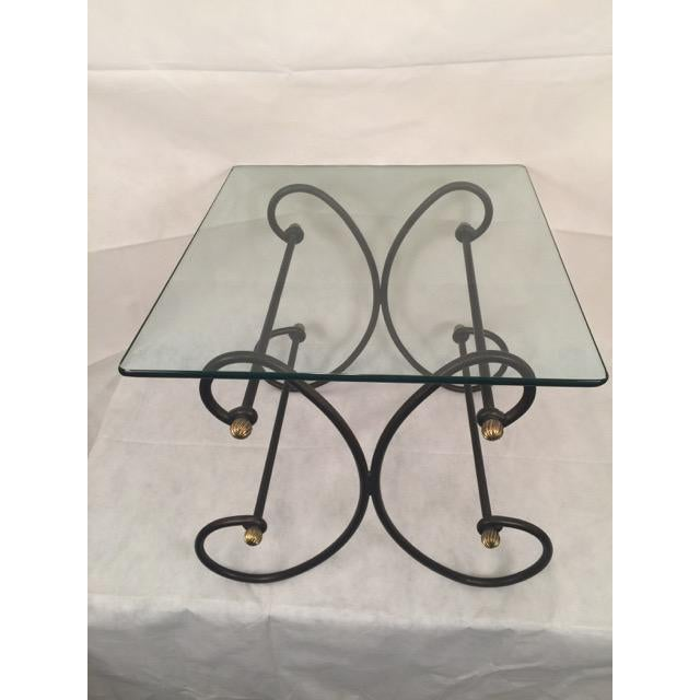 A vintage 1950's wrought iron and beveled glass side table is available for sale. The thick beveled glass top floats on...