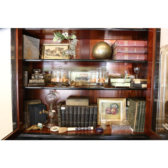 This is a gorgeous statement piece! An ebonized wood deus corps style bookshelf with glass doors on top and solid faced-...