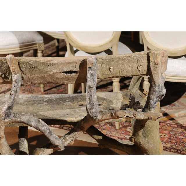 A French rustic faux-bois concrete garden bench from the late 19th century, with flower vases adorning each end....