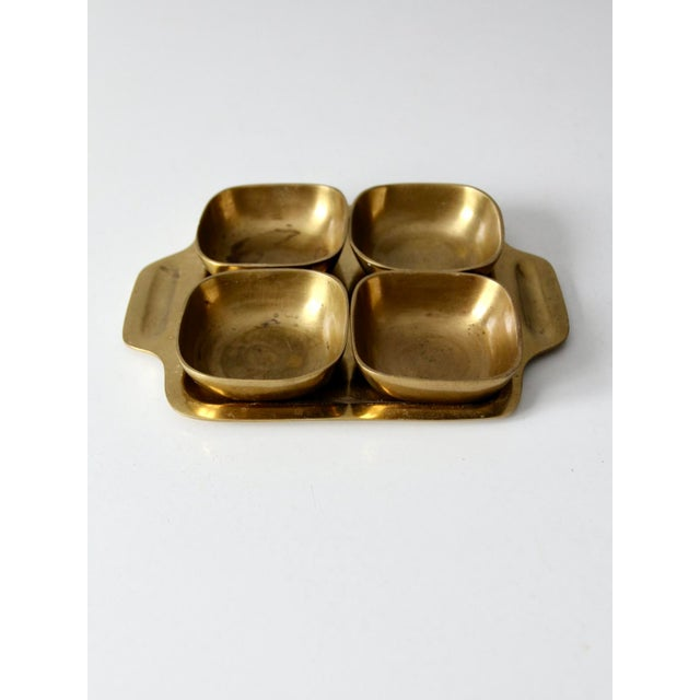 This is a vintage brass tray with bowls. The small brass tray features clean lines and slender handles at the side. Four...