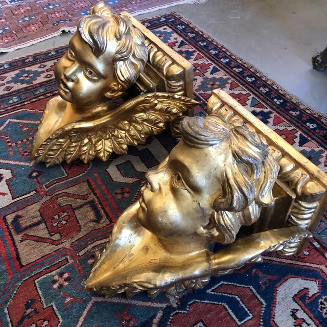 Pair of Italian antique baroque style wall bracket cherub/putti corbels. Carved wood with gesso, bole and gold leaf. Age...