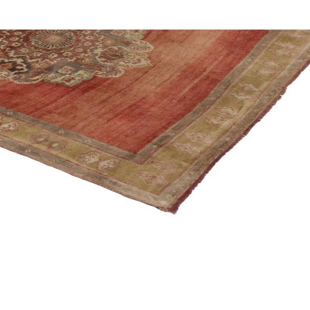 Three dominant medallions quietly float on the abrashed red field of this beautiful vintage Turkish Oushak carpet runner....