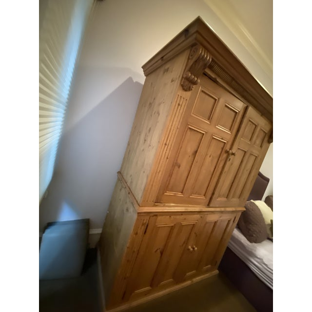 This lovely honey-coloured pine armoire from Europe circa 1880, has two doors with recessed panels that are on retractable...