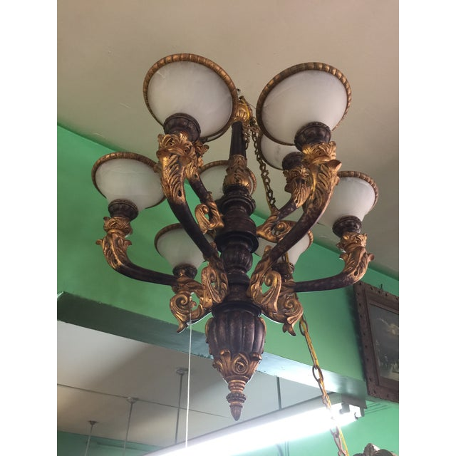 Carved wood chandelier with alabaster shades. This carved wood piece is polychrome decorated and comes with a decorative...