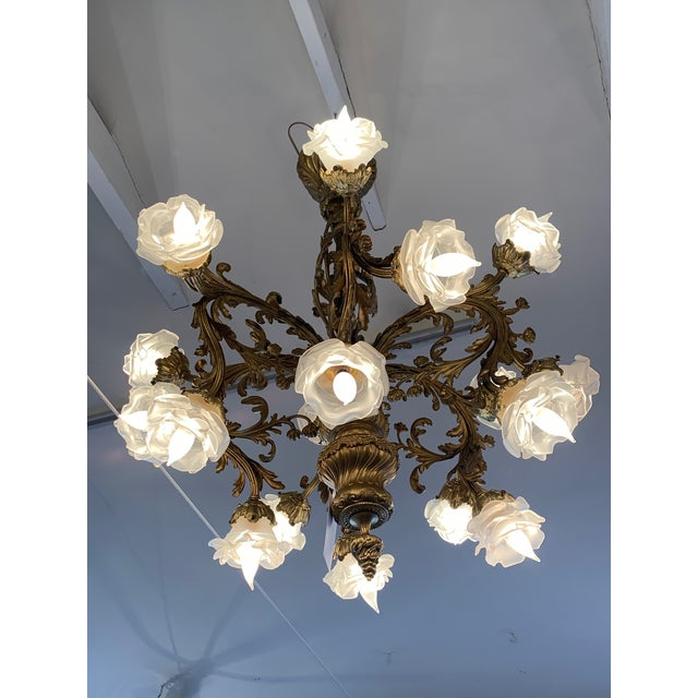 An ornate French Rococo style relief cast gilt bronze 18-light chandelier having frosted glass floral shades in the style...