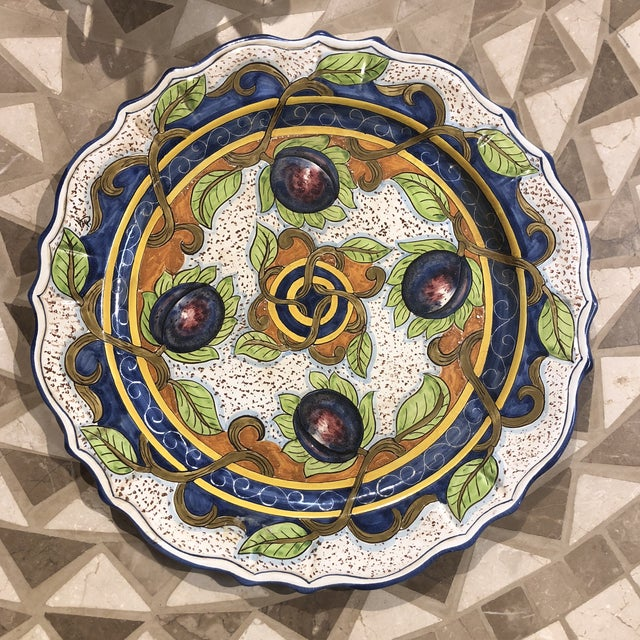 Hand painted ceramic wall plate with plum design in blue, green, and yellow colors. Hand made items may vary in size,...