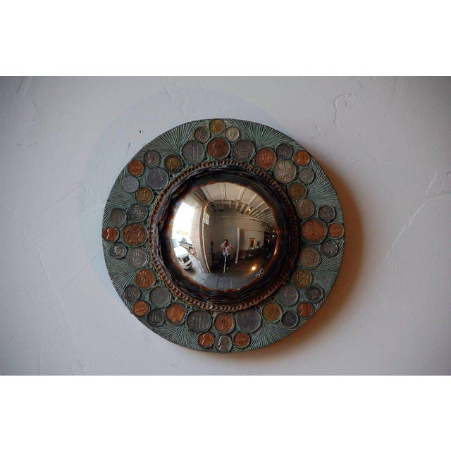 Small resin convex mirror with coin inclusions.