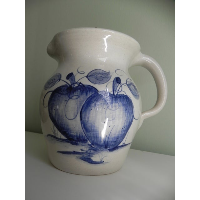 A utilitarian pitcher, hand-thrown from Yesteryears Pottery of Marshall, Texas. The apple motif in blue is eye-catching.