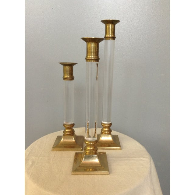 Add a touch of sparkle and elegance to your dining table or mantle with this trio of brass and lucite candlesticks. The...