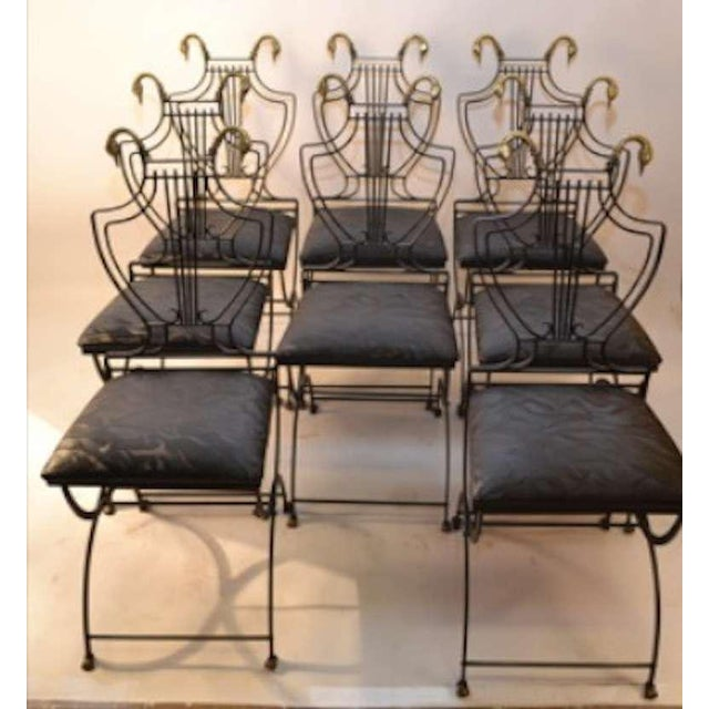 """Collapsible steel frame chairs, with brass swan head """"finials"""" and brass feet. Interesting mechanical furniture concept..."""