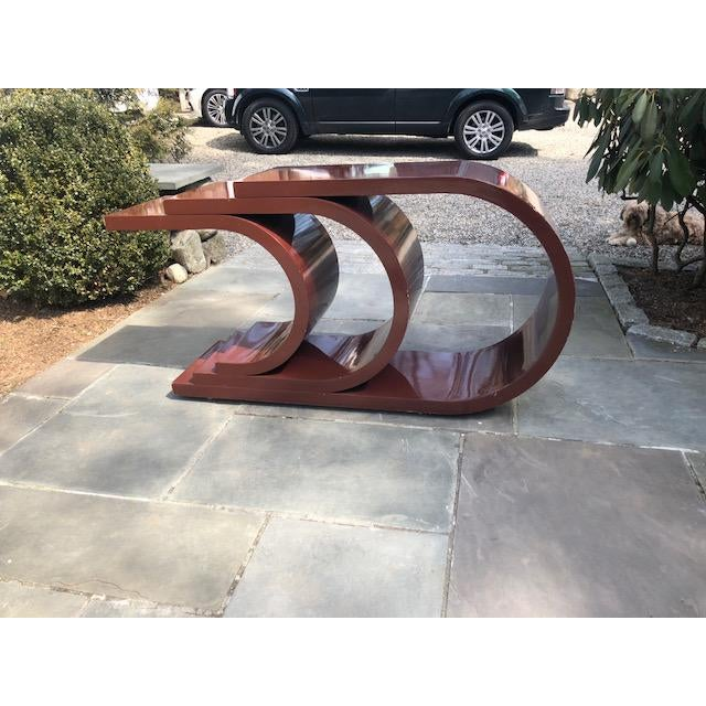 Unique mid century sculptural lacquer console table. This 1970's glossy Bordeuax laquer console table is the perfect mid...