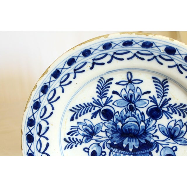 """A lovely Delft soup plate, c. 1800-1820. Decorated with an urn of flowers. Good condition. Typical rim frits. 9 1/8"""" dia."""