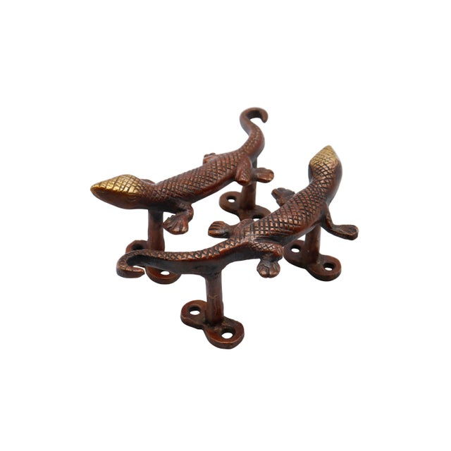 A pair of red brass lizard door handles or cabinet pulls. Pressed with simple details to convey skin, eyes and toes....