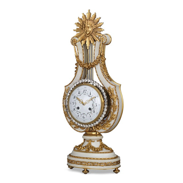 Exquisite hand-chiseled ormolu and white marble houses this exceptional French lyre clock. The opulent Louis XVI-style...