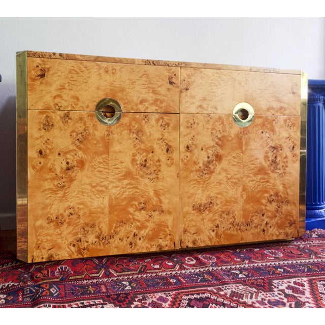 Beautiful sideboard of olive burl veneer with brass hardware and embellishments. This piece has a shorter footprint than...