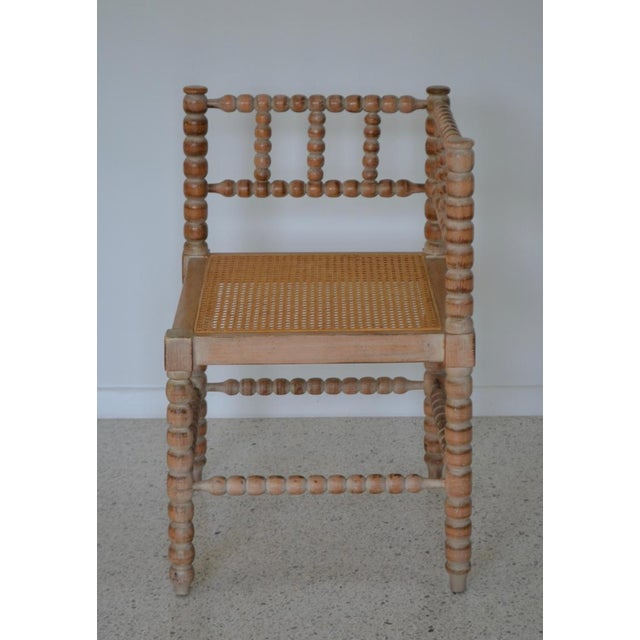 Striking turned wood corner chair with woven cane seat and sheepskin cushion, circa 1950s. This handcrafted solid hardwood...