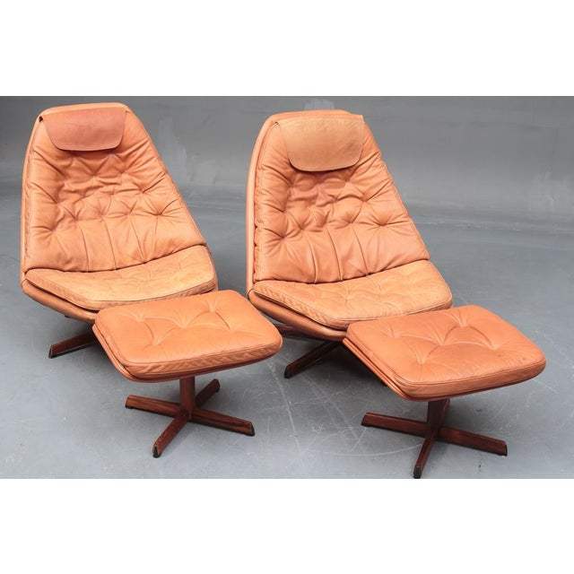 Pair of Danish 1960s Leather Upholstered Swivel Chairs with Figured Rosewood Bases and Matching Ottomans. The chairs by...
