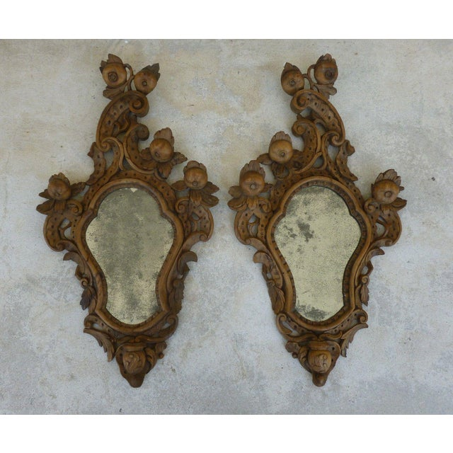 A fine pair of 19th c Italian Venetian Rococo wood mirrors with fruits and curly cues with a place for a candle at the...