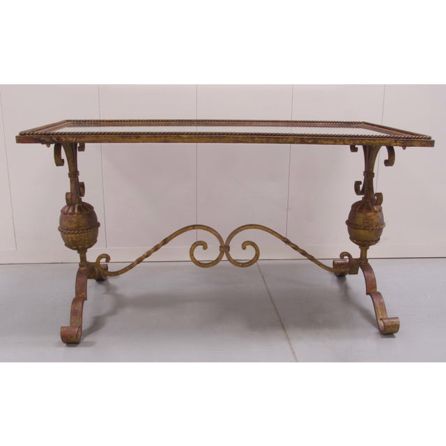 Patinated hand wrought iron coffee table with mirrored top. Decorative scroll base with elliptical drum style features....