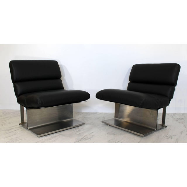 For your consideration is a magnificent pair of steel and black leather hide lounge chairs, by Paul Geoffroy by Uginox,...