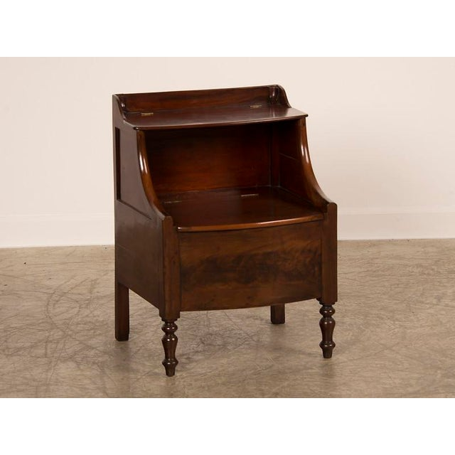 A William IV period mahogany side cupboard with two lift lids having a bow front and turned front legs from England c. 1840.